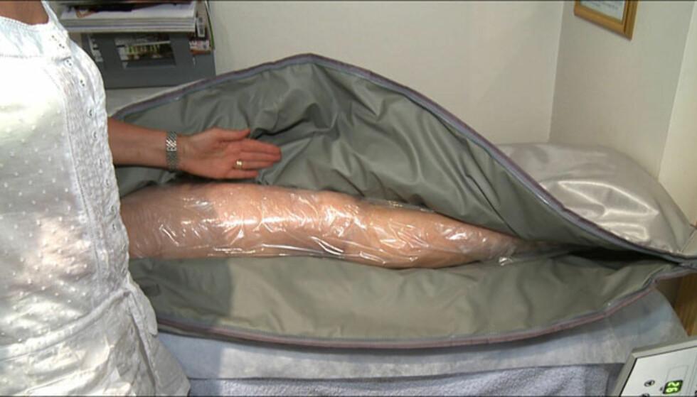 Klienten smøres inn med en krem som skal løse opp fett og cellulitter, samt stramme opp huden. Deretter pakkes hun inn i varmeførende folie, før hun blir lagt i en pose med infrarød varme.    Foto: Per Ervland