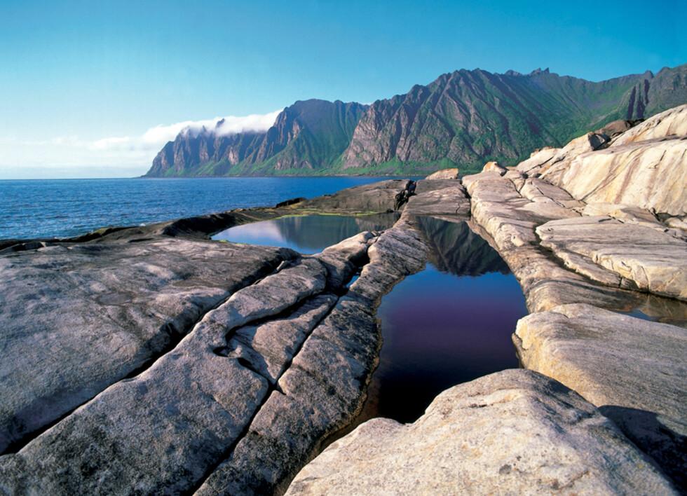 Her fra Tungesneset i Ersfjord på Senja. De blankskurte svabergene med alle jettegrytene ligger nydelig til ned mot havet, med øyas villeste fjellrekke midt imot. Ersfjord er et lite, vakkert sted med den fineste badestranda i Troms. Foto: Frithjof Fure Foto: Frithjof Fure