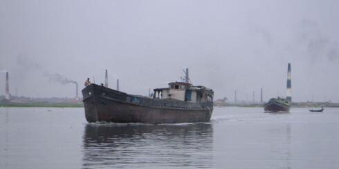 Båter på den forurensede Hariganga-elva med dampende fabrikker i bakgrunnen. Foto: wikipedia.com Foto: wikipedia.com