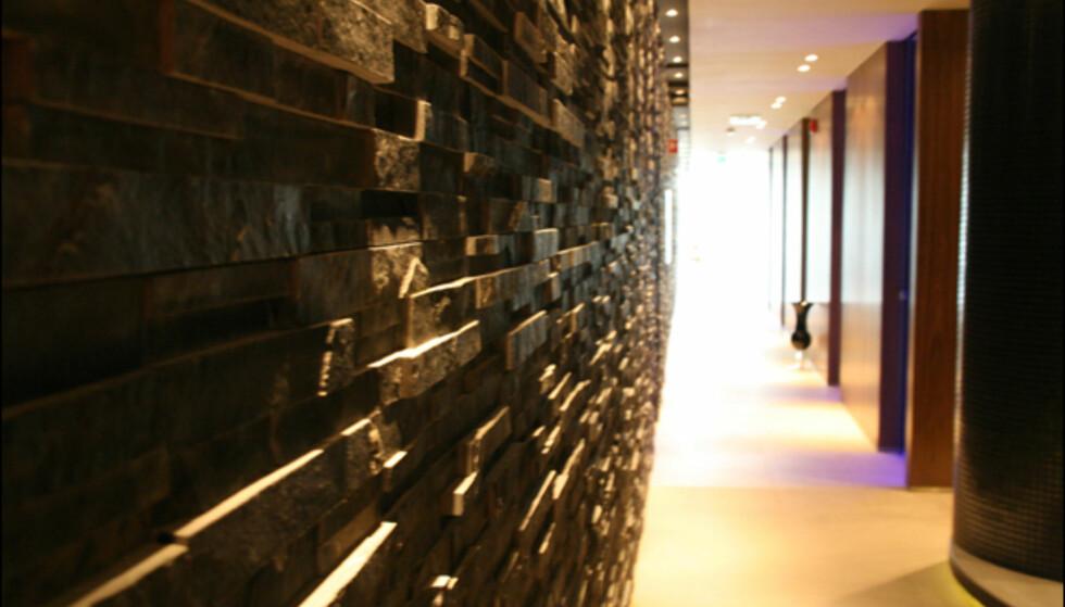Det er utbredt bruk av skifer på veggene. Behandlingsrommene på rekke inn til høyre.