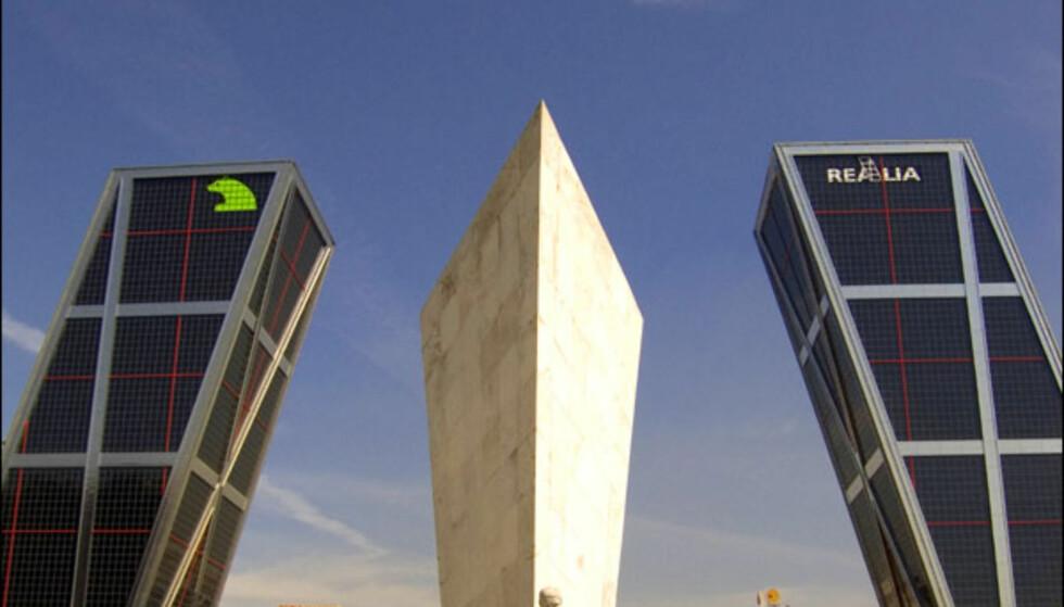 TORRES KIO, MADRID: Ay, Spania! Spanjolene elsker å kle seg opp og de kler gjerne opp byene sine. Torres KIO er vel et eksempel på arkitektur som skiller seg ut fra alt man har sett. Forestill deg tårnet i Pisa ganger to ikledd en Star Wars-kostyme og du får Torres KIO eller Europatårn I og II. Byggene er nemlig nemlig skråstilte. Det arkitektene Philip Johnson og John Burgee som har tegnet bygningene, mens Kuwait Investment Office (KIO) har finansiert bygningene. De to arkitektene arbeidet sammen i en periode på over 20 år fra 1967. De to står bak flere bygninger som i stor grad skiller seg ut i form og uttrykk. Johnson døde 99 år gammel i 2005, da hadde han blant annet fått Pritzker Architecture Prize Laureate. ADRESSE: Plaza de Castilla