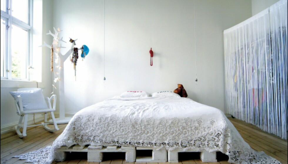 Leiligheten til scenografene og interiørstylistene Jannicke Kråkvik og Alessandro D'Orazio er en salig, fargerik blanding av markedsfunn, gjenbruk og nye designmøbler. Sengen har de fikset selv, det er en madrass, lagt på hvitmalte paller.   - Vi er opptatt av at ingen dører skal være lukket, og at soverommet skal være en del av leiligheten.  Foto: Erle Kyllingmark/IKKE BRUK