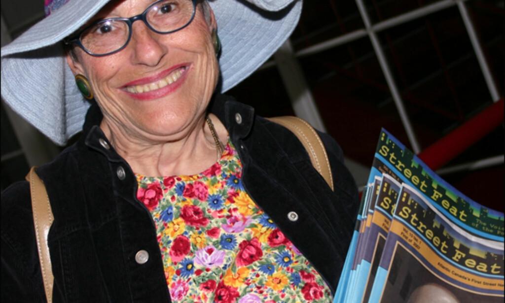 Judy Deal er lokal journalistspire og fast inventar på bondemarkedet. Der selger hun den uavhengige lokalavisa Street Feat, som hun selv skriver for. - Jeg hadde kreft og var veldig syk for noen år siden. Men så møtte jeg folka i Street Wise, og begynte å skrive for dem. De ga meg både håp og oppmuntring, sier den svært så glade og fargerike damen. Foto: Kim Jansson