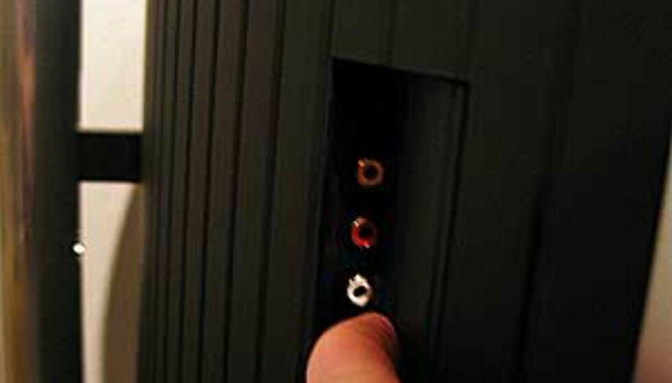 Inngangene på siden av TVen er skjult bak et vippedeksel.