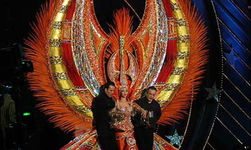 Kostymet er ikke til å gå i - her må det muskelhjelp til for å få damen ut på scenen. Foto: www.laspalmascarnaval.com Foto: www.laspalmascarnaval.com