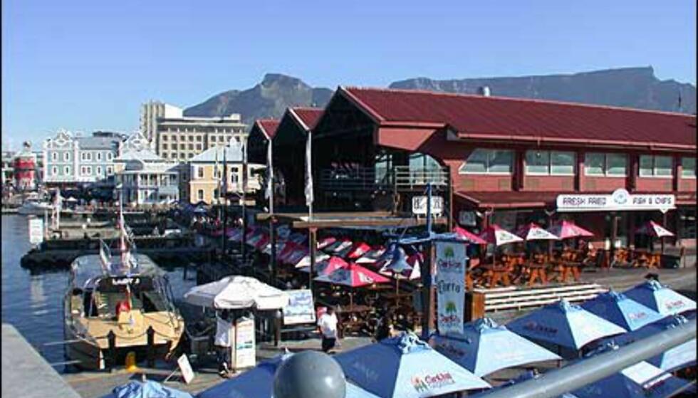 Victoria & Albert Waterfront med Table Mountain i bakgrunnen. Dette er kåret til en av Sør-Afrikas viktigste turistdestinasjoner. Her er det trygt og sikkert, masser av shoppingmuligheter, en levende havn, uteservering og ordinære restauranter og sprudlende folkeliv. Herfra går også båten til Robben Island der Nelson Mandela og andre politiske fanger satt i årevis.
