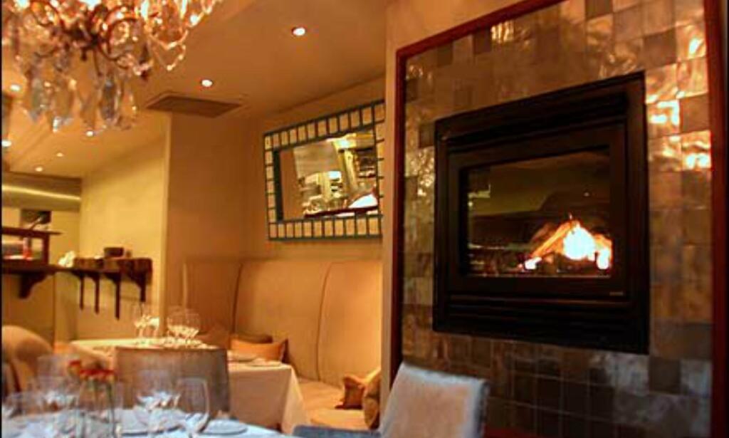 Bord rett ved peisen, som forøvrig er rammet inn av fliser i gullignende finish.