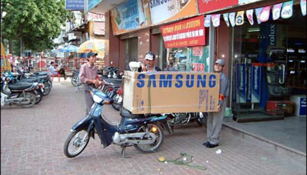 Fotograf og innsender, Morten Fossdal, skriver:  Disse bildene er tatt i Hanoi desember 02 i forbindelse med et bistandsprosjekt hvor vi satte opp en balløkke på en skole. De viser et par eksempler på de utroligste bruksområdene for sykkel og moped. Det ene er faktisk et nytt kjøleskap som blir fraktet på denne måten fra butikken. Kanskje ikke så rart at det omkommer over 20 personer i trafikken i Hanoi by hver dag. Foto: Morten Fossdal