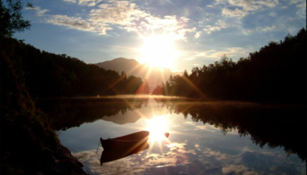 Bilde innsendt av Kenneth Sundnes.  -Bildet er tatt på vei hjem fra nattevakt/sommerjobb - sommeren 2002 utenfor Bodø. Står man tidlig opp eller går sent i seng, kan man fange solen der den ellers ikke pleier å være. Her er solen er på vei opp, mens den speiler seg i glansen av det blikkstille vannet, skriver Sundnes.  Foto: Kenneth Sundnes