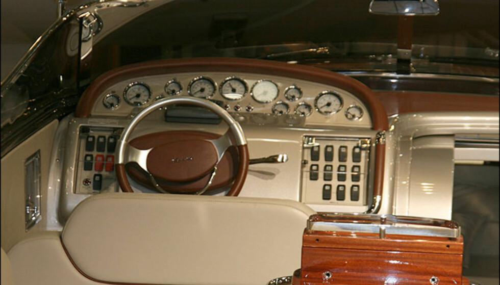 Riva førerplass. Den klassiske lykten på venstre side, gass- og girspak på rattet og bakspeilet er på plass. Speilet brukes til å se på de som soler seg bak på båten...