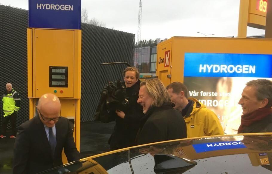 FØRSTE TANK: Det var klima- og miljøminister Vidar Helgesen (til venstre), som fikk æren av å fylle hydrogen på tanken til en Toyota Mirai, assistert av Colonialmajor Odd Reitan. Foto: Knut Moberg