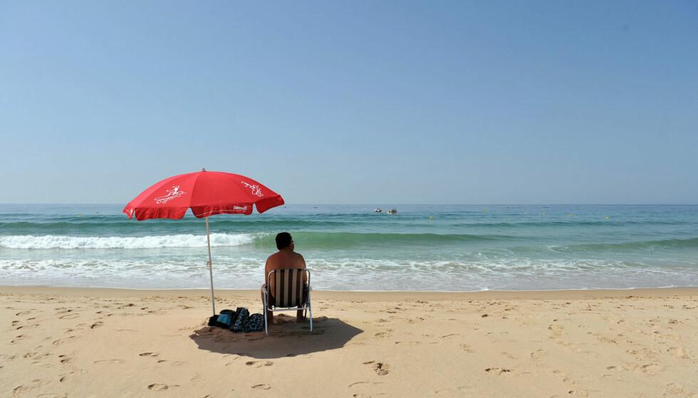 PORTUGAL: Hvis du vil få mye for pengene i sommerferien, er det ikke dumt å legge turen til for eksempel Portugal, tipser ekspertene. Mannen på bildet slikker sol på stranden Praia da Luz. Foto: NTB Scanpix.