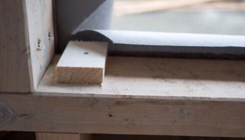 KLOSS: Sett noen klosser på karmen som vinduet settes oppå. Du kan få kjøpt ferdige plastklosser som er nøyaktige. Det er viktig at alle klossene ligger i vater. FOTO: Simen Søvik