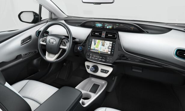 HYBRID-STILEN: Interiøret på nye generasjon Prius er selvsagt helt nytt, men en del av de originale stilelementene som den lille girhendelen og det sentralt og høyt monterte digitalpanelet, går igjen. Foto: Toyota