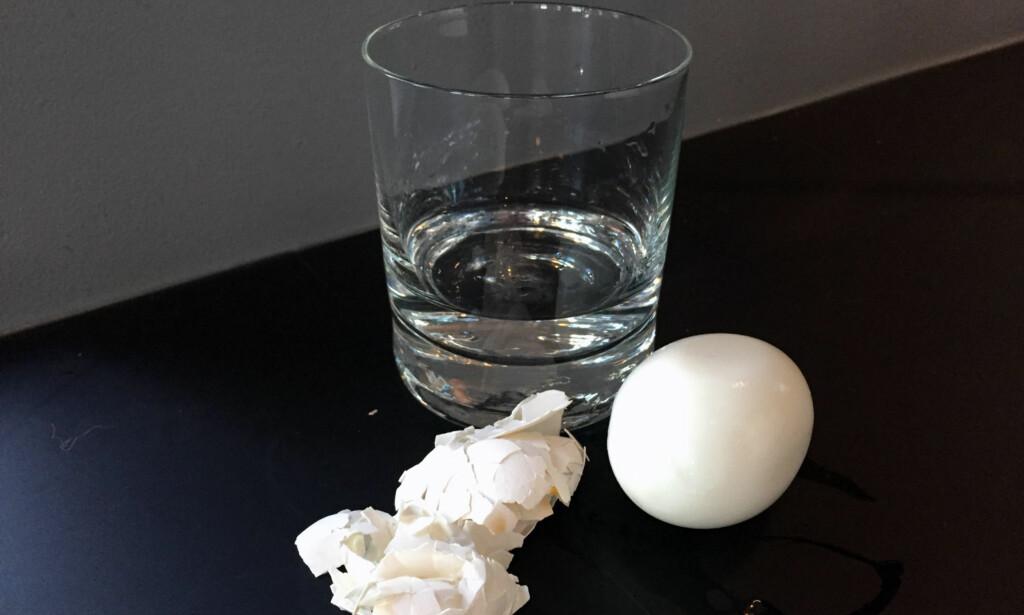 GLASS-METODEN: Du trenget et bredt vannglass med litt vann i, så er det bare å legge egget oppi, holde over glasset og riste i noen sekunder. Vi testet trikset, se hvordan det gikk i videoen nederst i artikkelen. Foto: Linn M. Rognø.