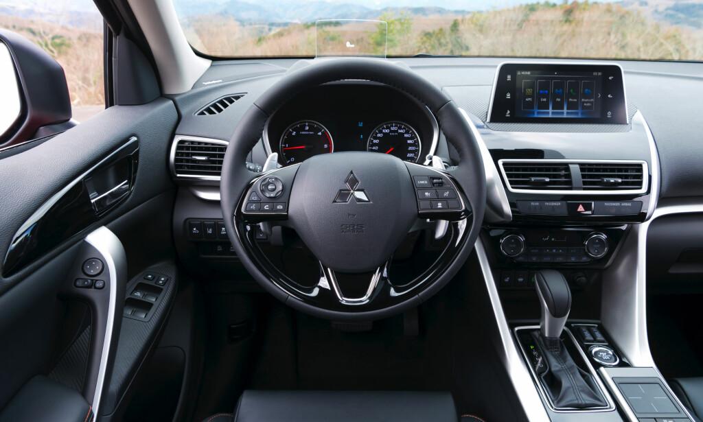 KLASSISK: Interiøret er en modernisert versjon av kjent Mitsubishi-stil. Her finnes både smarttelefonintegrering og en touchpad i midtkonsollen, samt head-up-display for informasjon i synsfeltet i frontruten. Foto: Mitsubishi