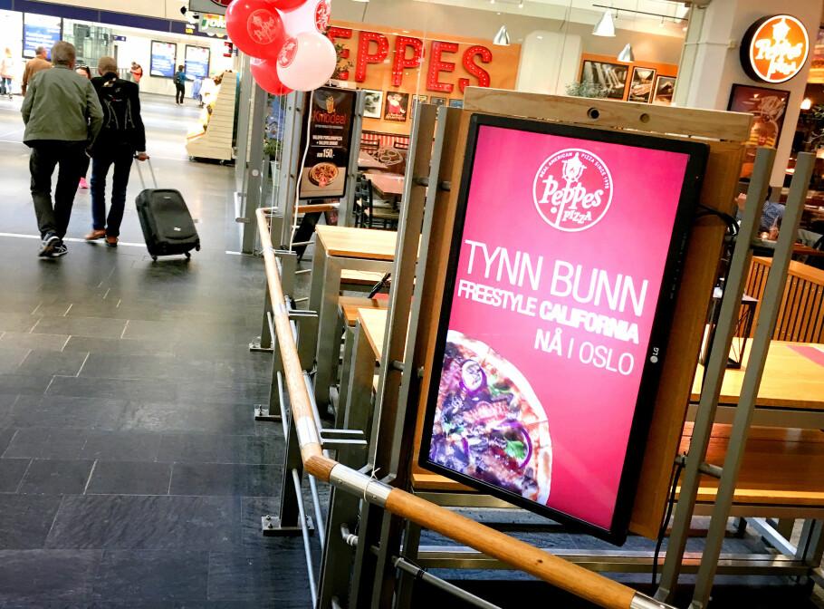 FØLGER MED: Dette reklameskiltet utenfor Peppes Pizza på Oslo S filmer fjeset ditt, og finner ut hvor gammel du er, og hvilket kjønn du har. Skiltet skal så vise deg en reklame som passer til dette. Legg merke til kameraet i toppen av skiltet. Foto: Ole Petter Baugerød Stokke