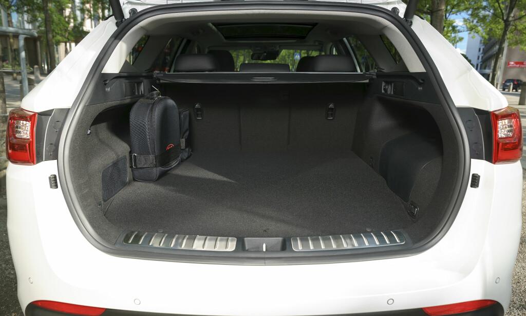 MOTBAKKE: Gulvet er litt høyere enn dieselbilen. Setene legges ned ved å trekke i spakene på siden. Foto: Kia