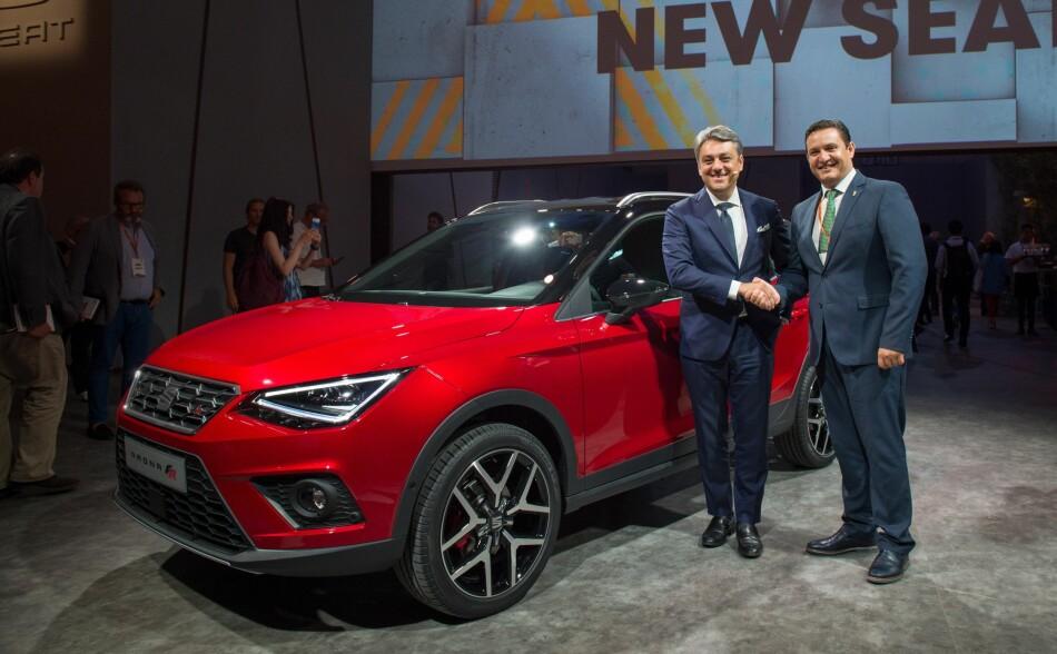 FØRST UTE: Her viser Seat-sjef Luca de Meo frem den nye kompakt-SUV-en, som har fått sitt navn etter en liten by på Tenerife - Arona. Sammen med ham står Aronas borgermester. Dermed kommer den spanske konstruktøren først av VW-gruppens merker med en såkalt B-segment-SUV. Foto: Seat