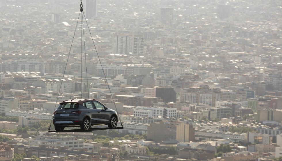 SPEKTAKULÆRT: Lanseringen av Arona i Barcelona foregikk ved at bilen ble båret over byen i helikopter. Som PR-stunt ble det utvilsomt lagt merke til lokalt. Seat har hovedkvarter og fabrikker i Barcelona-området i Catalonia. Foto: Seat