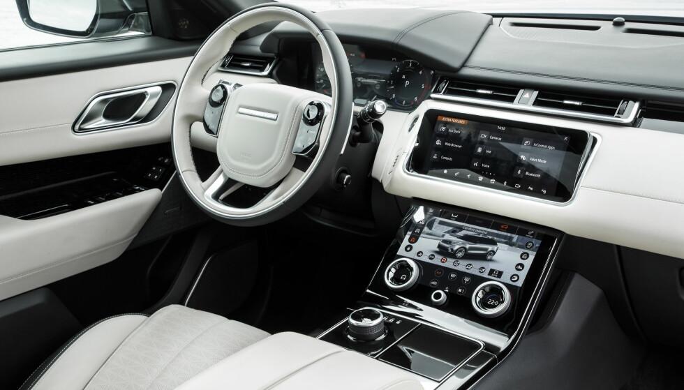 LEKKERT: Alle tre skjermer samt betjeningen på rattet er speilblankt og sort før du starter bilen. Det er to koppeholdere og ekstra rom, samt grei lagringsplass under armlenet. Bak nedre skjerm er det et hull bak, slik Volvo nylig gikk bort fra. Foto: Land Rover