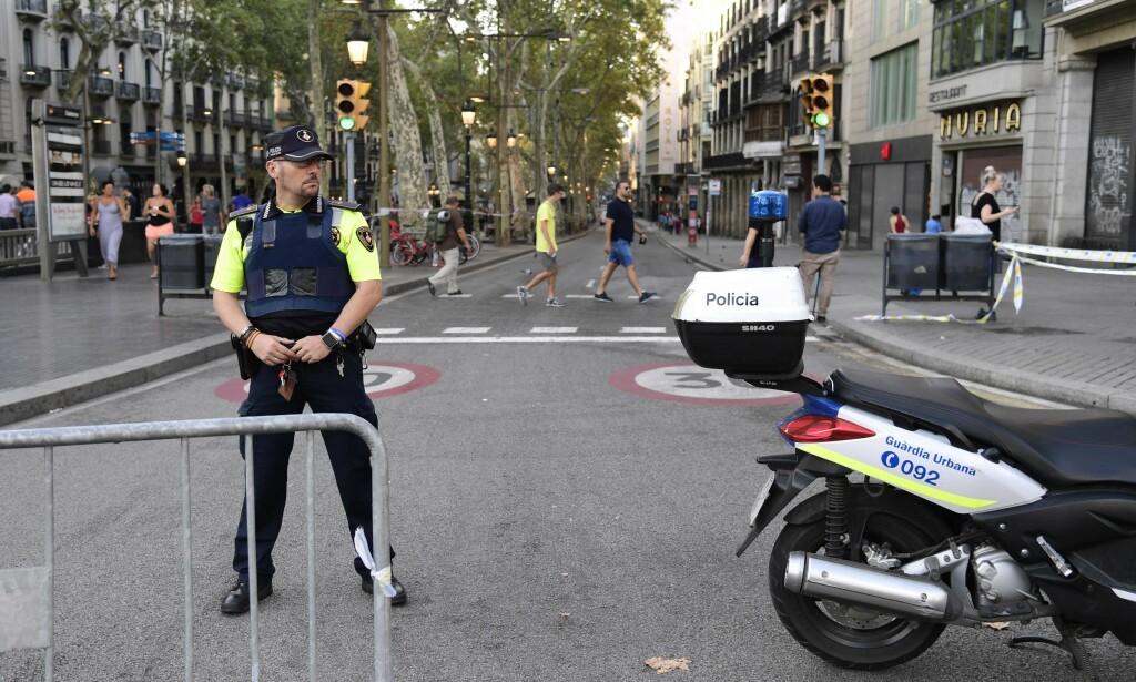 TERROR I BARCELONA: En spansk politimann står vakt på La Rambla etter torsdagens terrorangrep. Foto: AFP