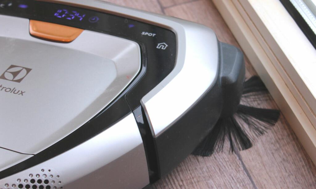 KOMMER GODT TIL: Fasongen på roboten og denne kosten som surrer rundt i et hjørne, gjør at den får feid frem og tatt opp mye rusk som ligger i hjørner, inntil kanter og tepper. Det er bra. Foto: Kristin Sørdal