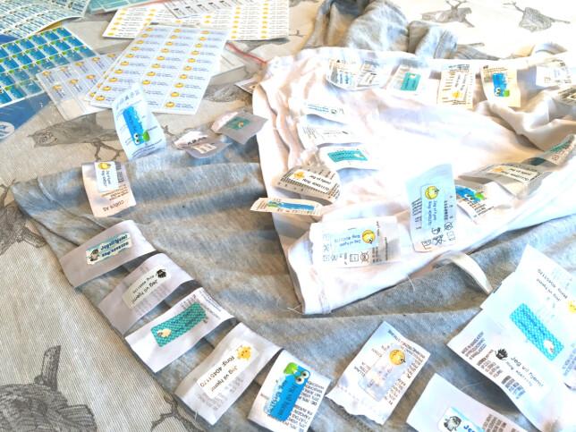 SLIK HAR VI TESTET KLES-LAPPENE: Det anbefales å feste merkelappene på vaskelappen i plagget. For å unngå eventuelle forskjeller på vaskelappenes hefteevne, har vi tatt vaskelapper fra plagg fra samme produsent og festet dem på de samme genserene. Vi har testet lappene på vaskelapper fra flere klesprodusenter. Foto: Kristin Sørdal
