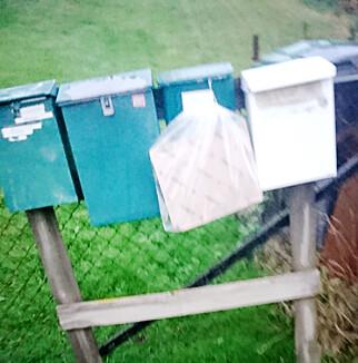 HENGENDE: Her er en PostNord-pakke hengt utenpå postkassa. Dette skal være i henhold til rutinene. Foto: Stian Sandland