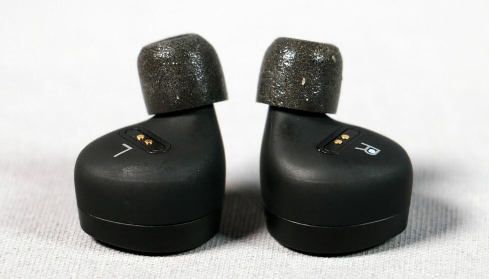 VRIS INN: Beoplay E8 stikkes inn i øret og vris på plass, slik at de sorte klumpene hviler på innersiden av øret. Foto: Pål Joakim Pollen