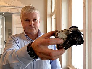 Odd Magne Skjerping i Frende forsikring viser frem en utbrent røykvarsler som manglet batteri. Foto: Frende forsikring