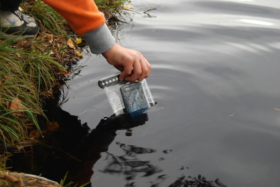 NERVØSE Ville du tatt sjansen på å la et barn senke ned iPhonen din ned i et vann?  Foto: Thomas Strzelecki