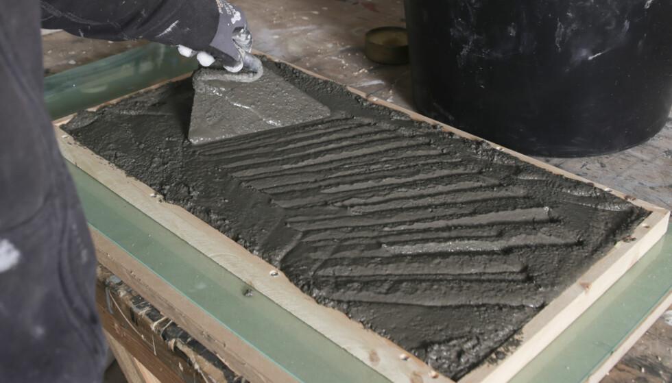 Legg i betongen: Bruk murerskje og legg i betongen, pass på at ikke nettet flytter seg. Jobb blandingen godt ned i formen. Foto: Øivind Lie-Jacobsen