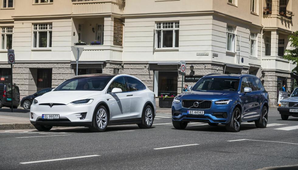 EN KAN FORBYS: Regjeringens klimaplan kommer til å åpne for å forby fossilbiler i enkelte bysoner. Det vil i så fall gjøre at Volvo XC90 (t.h.) ikke kan kjøre der, mens Tesla Model X (t.v.) får enda mer byplass å boltre seg på. Foto: Jamieson Pothcary