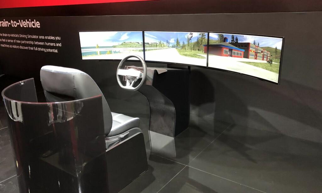 HJERNEN STYRER: Her på elektronikkmessen CES i Las Vegas, står en simulator der de besøkende kan forsøke den nye teknologien som ifølge bilprodusenten Nissan lar hjerneaktiviteten bidra til en sikrere kjøreopplevelse. Foto: Bjørn Eirik Loftås