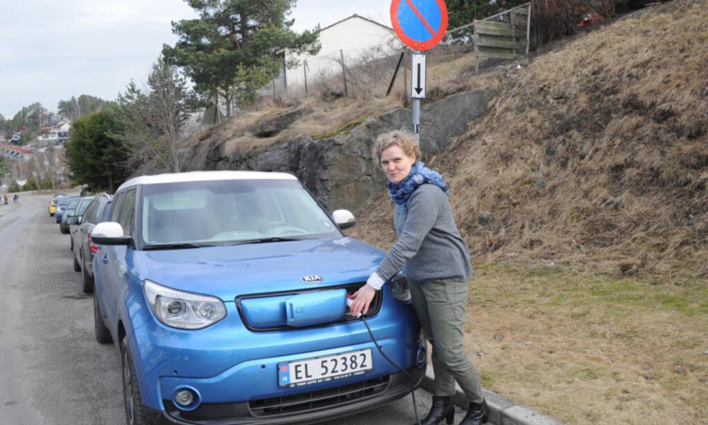 LADET I SMUG: Gro Rebnord på Holmlia i Oslo måtte feilparkere og strekke ledning ut av vinduet på leiligheten sin for å få ladet elbilen sin. Foto: Tore Neset