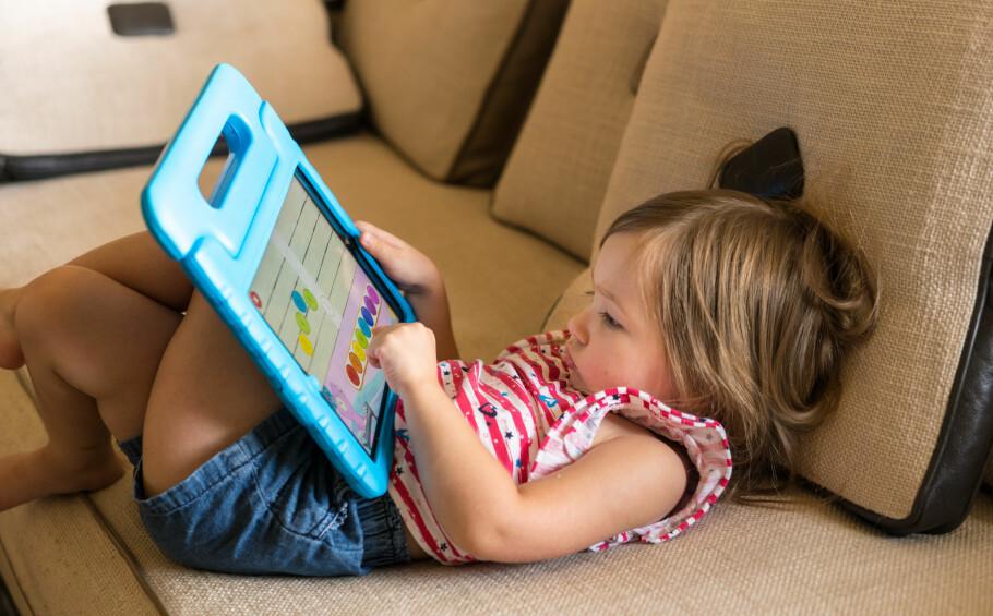 VANLIG SYN: Mange barn i dag er å finne sånn rundt omkring i hjemmet. Men har du sørget for å barnesikre nettbrettet eller mobilen før de har begynt å bruke den? Foto: Shutterstock