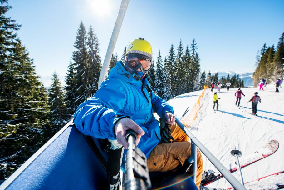 DÅRLIG IDE: Å bruke mobilen i skiheisen er bare ett av mange eksempler på ting du ikke burde gjøre i vinter. Mister du den, mister du også forsikringsdekningen. Foto: Shutterstock / NTB Scanpix