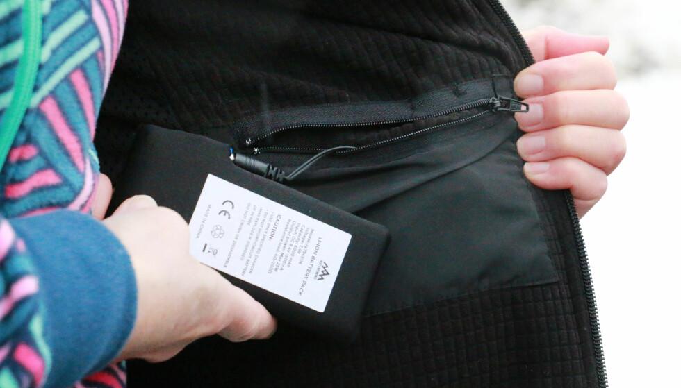 BATTERILOMME: Batteriet må lades før bruk. Det kobles til via en ledning i batterilommen på innsiden av vesten. Foto: Ole Petter Baugerød Stokke