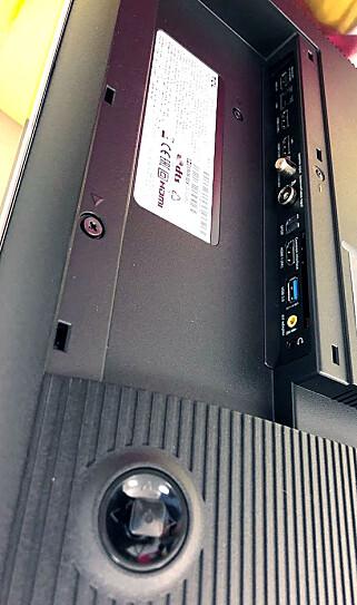 TILKOBLINGER: TV-en byr på godt med tilkoblingsmuligheter, alle kontaktene sitter vertikalt bak et lokk på baksiden. Joysticken nederst brukes hvis du ikke finner fjernkontrollen. Foto: Bjørn Eirik Loftås