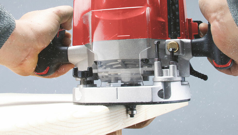 HÅNDOVERFRES: Fresestålet spinner rundt i en voldsom hastighet og gir bordplaten en pen avrunding. Det lille, blanke hjulet nederst på fresestålet ruller på kanten og styrer dybden på fresingen. Foto: Makita