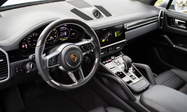 STRIKT: Porsche har alltid vært veldig nøkterne på interiørfronten. Selv om det meste nå er skjermer og blanke berøringsflater, er innrammingen så tradisjonell at dette ikke føles nytt lenger. E-Hybrid kjennetegnes med grønne målernåler og flere separate skjermvisninger for hybridfunksjonene. Foto: Porsche.