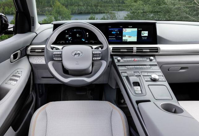 «FLIGHT-DECK»: Den massive konsollen er fylt med en mengde knapper som betjener bilens ulike systemer og dessuten et dreiehjul for valg av funksjoner på den sentralt plasserte skjermen på 12,3-tommer. Til venstre for rattet finner vi enda flere knapper. Økologiske materialer i seter, dørpanel og ratt. Foto: Hyundai