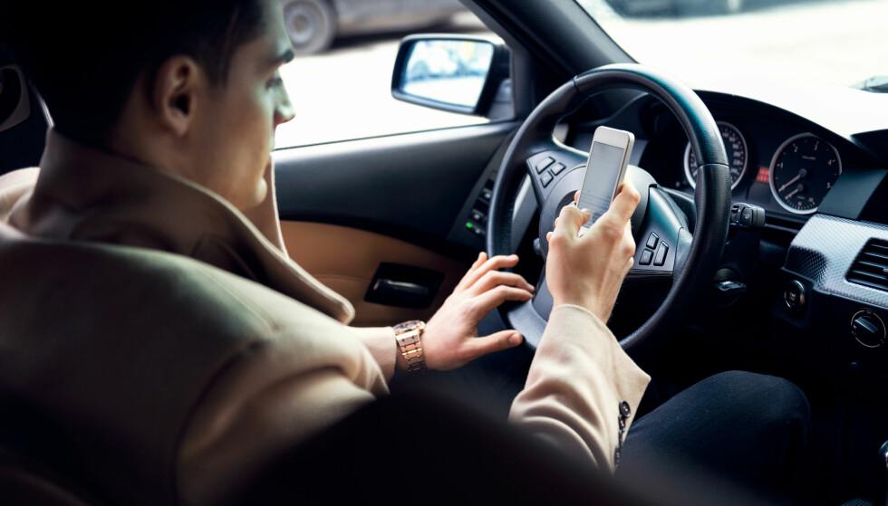 KJØRER ULOVLIG: Seks av ti i husstander som tjener mer enn 1,5 millioner kroner i året innrømmer at det hender de bruker mobiltelefon uten handsfee, når de kjører bil. Foto: Shutterstock