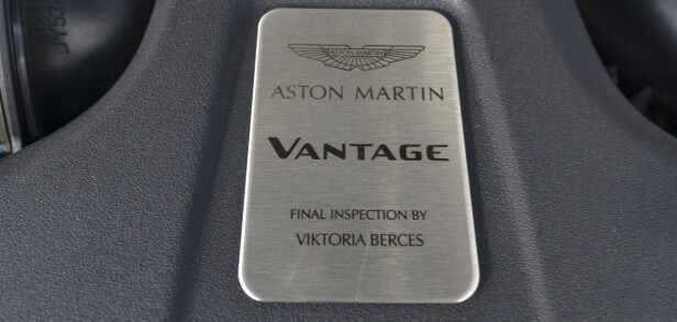 V8 Biturbo: Vantage bruker AMG-s fantastiske 4-liters V8 md doble turboer. Den blir bygget av en mann hos AMG og signeres, men Aston Martin ønsket ikke noen spor av AMG og har laget en egen plakett. Victoria Berces har tydligvis inspisert motoren etter ankomst hos Aston Martin. Foto: Jamieson Pothecary