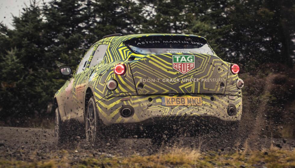 SÅ GJØRMA SPRUTER: Dette maskerte eksemplaret av den kommende Aston Martin-SUV-en er observert i Wales, der Rally Wales kjøres hver vinter. Foto: Aston Martin