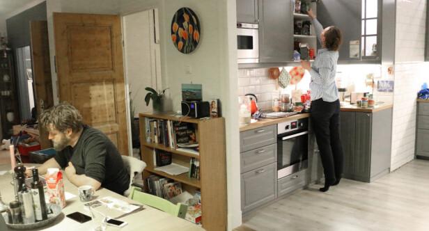 <strong>MULTITASKING:</strong> Morten sitter ved spisebordet og skriver handleliste, mens Anne-Martha ser hva de har stående helt innerst i skapet. Hun finner ut at de har «kokosmelk for resten av året», som familien løser med en indisk middagsrett denne uka. Foto: Eilin Lindvoll.