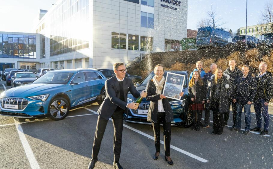 I JUBELRUS: Kommunikasjonssjef Morten Moum spretter champagnen sammen med Audi-direktør Elin Rosnes Sinervo for prisen. Trine Johansen– Digital Content Manager, Eirik Kristoffersen - Leder for Produktavdelingen, Bent Martinsen - Produktsjef, Benthe Saga – Produktsjef, Ole Andre Rognstad - Produktspesialist, Tommy Bækkevold Jensen – Markedssjef og Johan Ramstad - Produktsjef er strålende fornøyde med at våre lesere stemte frem Audi e-tron til Årets Bil og regner med å ha travle tider i møte. Foto: Per Ervland.