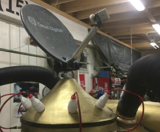 DIGITAL TV? Radar måtte vi ha, så vi bytta fra Canal Digital til RiksTV, så jeg har brukt parabolen til det. Med avkappa brusflaske og høyttalerledninger, fikk vi lynavleder. Rakettmotoren er en 50-liters kompressortank. Foto: Kaj Alver