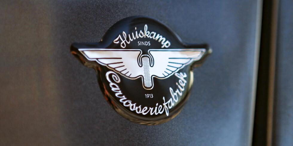 <strong>PRODUSENTEN:</strong> Huiskamp Carrosseriefabriek har lagt igjen noen sport etter seg selv. Her er logoen fra bakenden av Teslaen. Foto: Øystein Fossum
